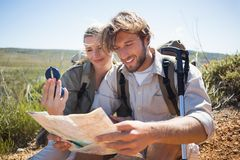 Hiking couple taking a break on mountain terrain using map and compass Royalty Free Stock Photography