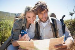 Hiking couple taking a break on mountain terrain using map and compass Royalty Free Stock Images