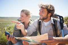 Hiking couple taking a break on mountain terrain using map and compass Stock Photo