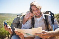 Hiking couple taking a break on mountain terrain using map and compass Royalty Free Stock Photos