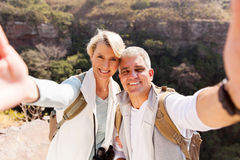 Hiking couple taking selfie. Happy hiking couple taking selfie together on top of mountain stock photography