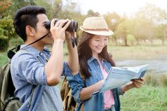 Hiking couple using binocular and map. Travel and explorer Royalty Free Stock Photography