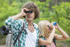 Hiking couple using binoculars in forest Stock Images