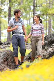 Hiking couple walking in forest. Young hikers couple enjoying romantic walk in spring forest with flowers. Happy smiling interracial couple holding hands Stock Image