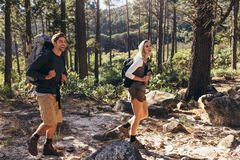 Hiking couple walking in forest wearing backpacks Stock Photography