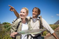 Hiking couple walking on mountain terrain looking at map Royalty Free Stock Images