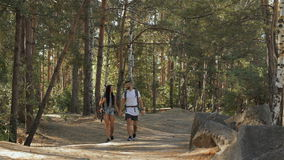 Hiking couple walks at the forest. Romantic hiking couple walking at the forest. Long shot of caucasian man and woman going across the the forest road. Slim stock video