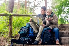Hiking couple having break on forest trail. Hiking couple, women and man, having break on a forest trail and reading the map royalty free stock photos