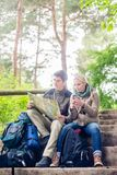 Hiking couple having break on forest trail. Hiking couple, women and man, having break on a forest trail and reading the map stock photo