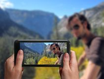 Young male hiker relaxing on top of a mountain.Hand is taking a photograph with a smartphone of the man together w. Hiking couple. Young male hiker relaxing on stock image