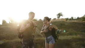 Hiking couple. Young woman and man hiker picking up their backpacks from the ground. Ready to go, enjoying their time. Together, smiling happy, holding hands stock video