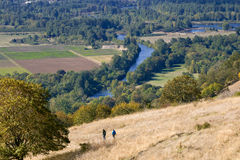 Hiking down from the hilltop. Two tiny figures are seen hiking down Mt. Pisgah in Eugene, Oregon. Far below we can see the Willamette River wending its way Royalty Free Stock Images