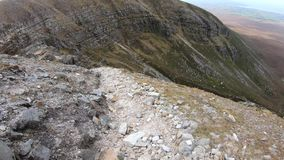 Hiking down Muckish mountain stock video