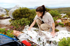 Hiking emergency. Medical emergency while hiking. women has emergency blanket and her friend is calling for help stock photo