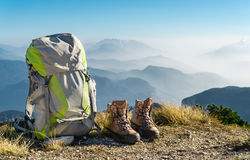 Hiking equipment. Backpack and boots on top of mountain. Hiking equipment. Backpack and boots on top of the mountain. Beautiful view to mountain ranges and fog Royalty Free Stock Photo