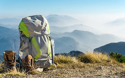 Hiking equipment. Backpack and boots on top of mountain. Royalty Free Stock Photography