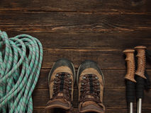 Hiking equipment  on dark wooden background, top view. Freedom c. Climbing equipment: blue rope, trekking shoes and other set  on dark wooden background, top Royalty Free Stock Image