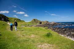 Hiking family, mother and child walks on green, grass covered field, North Ireland Stock Photo