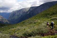 Hiking in fjord Norway. People hiking in the mountains with a fjord in the depth and sky with clouds Stock Images