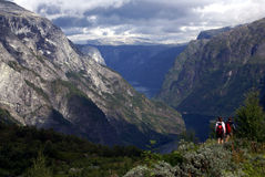 Hiking in fjord Norway. People hiking in the mountains of Norway with a fjord in the depth and sky with clouds stock image