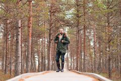 Hiking in forest. Camp, adventure, traveling concept. Bearded guy with backpack walking in swamps and enjoying the views. Camp, adventure, traveling and fishing royalty free stock photos