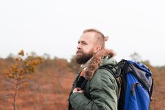 Hiking in forest. Camp, adventure, traveling concept. Bearded guy with backpack walking in swamps and enjoying the views. Camp, adventure, traveling and fishing royalty free stock images