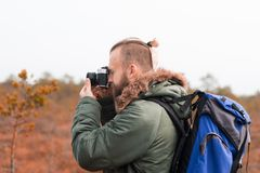 Hiking in forest. Camp, adventure, traveling concept. Bearded guy with backpack walking in swamps and taking pictures. Camp, adventure, traveling and fishing stock image