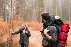 Hiking in forest. Camp, adventure, traveling concept. Two bearded guys with backpacks hiking in forest. Camp, adventure, traveling and fishing concept royalty free stock image