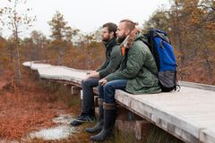 Hiking in forest. Camp, adventure, traveling concept. Two bearded guys with backpacks sitting in swamps. Camp, adventure, traveling and fishing concept royalty free stock photography