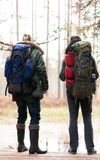 Hiking in forest. Camp, adventure, traveling concept. Two bearded guys with backpacks hiking in swamps. Camp, adventure, traveling and fishing concept stock photography