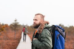 Hiking in forest. Camp, adventure, traveling concept. Two bearded guys with backpacks hiking in swamps. Camp, adventure, traveling and fishing concept royalty free stock images