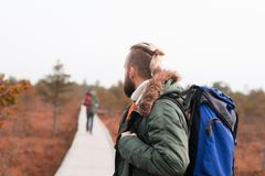 Hiking in forest. Camp, adventure, traveling concept. Two guys with backpacks walking in swamps in forest. Camp, adventure, traveling and fishing concept stock images