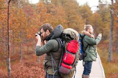 Hiking in forest. Camp, adventure, traveling concept. Two guys with backpacks walking in swamps and taking pictures. Camp, adventure, traveling and fishing royalty free stock image