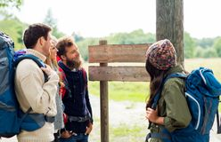 Hiking friends with backpacks at signpost. Travel, tourism, hiking and people concept - group of happy friends or travelers with backpacks looking at signpost royalty free stock photography