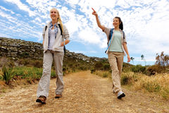 Hiking fun lifestyle. Friends walk a dirt road together outdoors, healthy hiking on a sunny day stock image