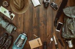 Hiking gear frame including machete, knife, clothes, boots, lantern, camera, hat, map, compass, mobile phone. Wanderlust, safari