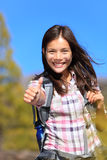 Hiking girl. Happy thumbs up smiling. Young Asian woman hiker smiling joyful at camera outdoor on hike trip. Beautiful young mixed race Asian Chinese / stock photo