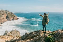 Hiking girl with backpack near the Atlantic Ocean in Portugal raises up her hands shows how pleased she is royalty free stock photography