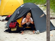 Hiking girl on the camp. Hiking girl making manicure on the camping on the beach near the tent Stock Photo