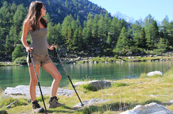 Hiking girl looks at alpine lake Royalty Free Stock Photos