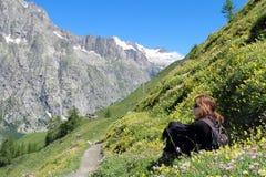 Hiking girl relaxing among mountain flowers Royalty Free Stock Photos