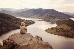 A hiking girl sits on the edge of the cliff and looking at the river and mountains. Location: the meanders of Arda river, Bulgaria Stock Photos