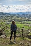 A hiking girl sits on the edge of the cliff and looking at the  valley and mountains Stock Photos