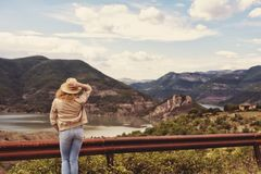 A hiking girl stands by the roadside and looking at the river and mountains. Location: the meanders of Arda river, Bulgaria Stock Photography