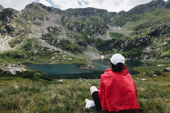 Hiking girl taking rest & relaxing in front of a mountain lake a Royalty Free Stock Photos