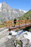 Hiking girl on a wooden mountain bridge Stock Photo