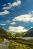 Hiking through Glendalough upper lake on a sunny day, County Wicklow, Ireland Royalty Free Stock Images
