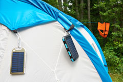 Hiking hand-held portable batteries solar panels on tent. Hiking hand-held portable batteries with solar panels on tent stock photography