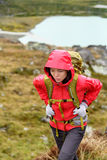 Hiking - hiker woman on trek with backpack in rain. Hiking - hiker woman on trek with backpack living healthy active lifestyle. Hiker girl walking on hike in royalty free stock image