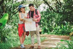 Hiking - hikers looking at map. Couple or friends navigating together smiling happy during camping travel hike outdoors in forest. Stock Images